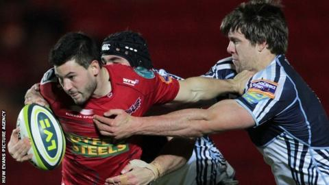 Scarlets' Dan Newton tries to break the tackle of Blues Michael Paterson and James Down
