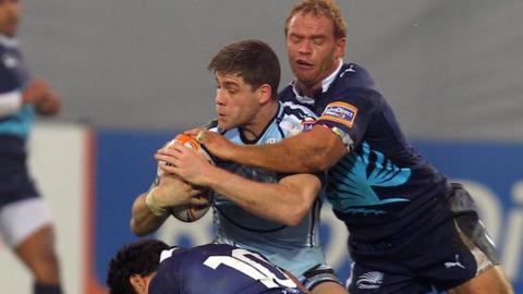 Blues centre Gavin Evans is wrapped up by Zebre fly-half Daniel Halangahu