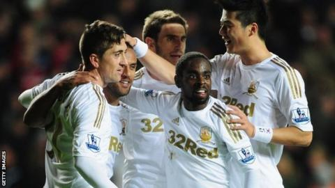 Swansea celebrate their third goal against West Brom