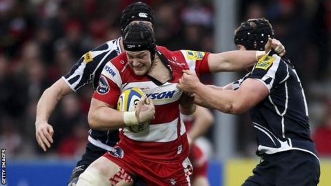 Tom Savage is tackled by two Sale Sharks players