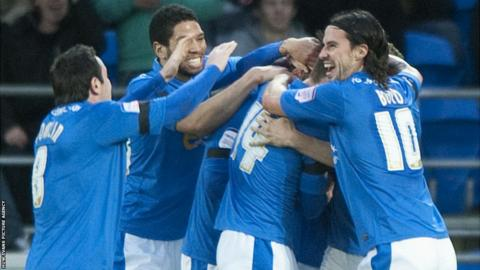 Peterborough players mob Michael Bostwick after he gives them the lead away to Cardiff City