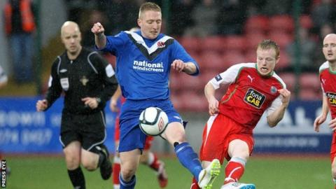 Crusaders midfielder Chris Morrow shields the ball from Cliftonville's George McMullan