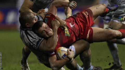 Scarlets' Tavis Knoyle is tackled by Cardiff Blues' Taufa'ao Filise