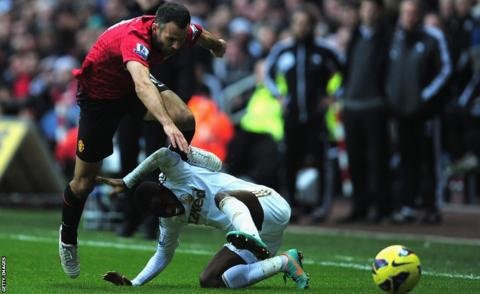 Manchester United substitute Ryan Giggs attempts to evade the tackle of Swansea City's Nathan Dyer in a game which ended 1-1 at the Liberty Stadium.