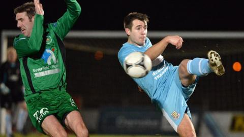 Andy Crawford of Ballinamallard United takes evasive action as Ballymena United's Ross Black clears the ball