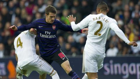 Arsenal's Cardiff-bred Welsh midfielder Aaron Ramsey battles for the ball against Swansea