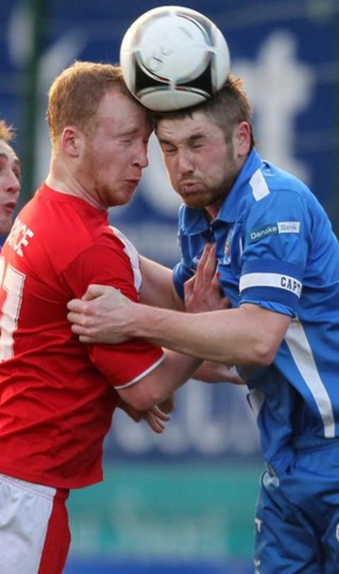 Liam Boyce and Mallards defender Mark Stafford go head-to-head during Cliftonville's 4-2 victory