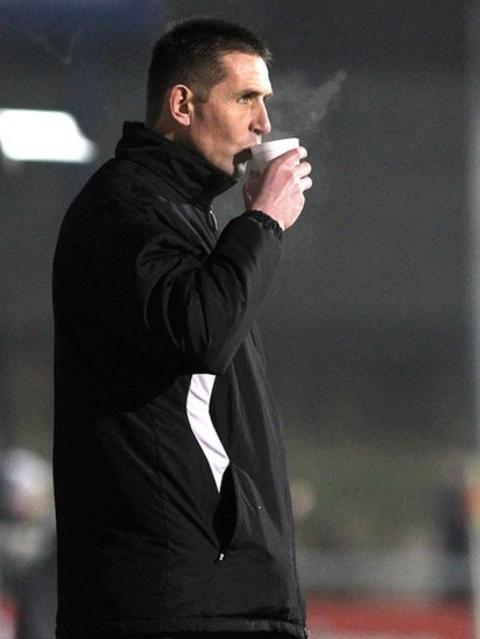 Crusaders manager Stephen Baxter stays warm with a cup of tea on the sideline