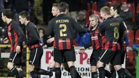 Crusaders players celebrate with Gary McCutcheon after his penalty kick levelled the score against Linfield at Seaview
