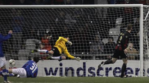 Crusaders striker Timmy Adamson scores past Linfield keeper Ross Glendinning to secure a place in the sixth round of the Irish Cup