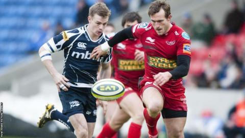 Scarlets' Andy Fenby holds of the challenge of Sale's Wales scrum-half Dwayne Peel, facing his former club, in the LV= Cup clash at Salford City Stadium.
