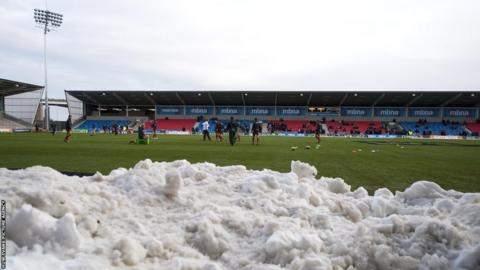 Scarlets players warm up for their LV= Cup match against Sale Sharks with snow piled around the Salford City Stadium pitch.