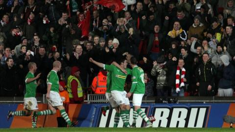 Diarmuid O'Carroll celebrates in front of the Cliftonville fans after scoring the opener