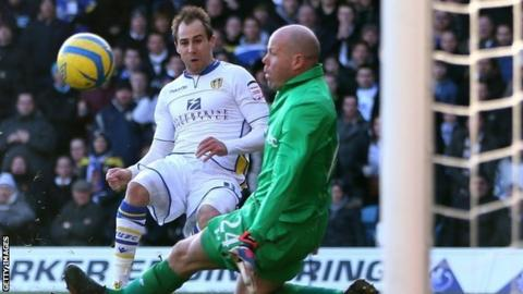 Luke Varney clips the ball past Brad Friedel to put Leeds ahead