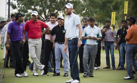 Rhys Davies is pictured with Indian cricket legend Sachin Tendulkar during a putting challenge at the Challenge Tour's Gujarat Kensville Challenge.