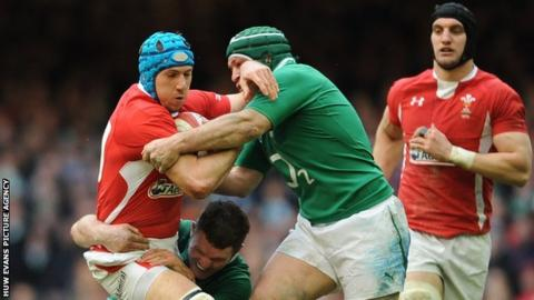 Justin Tipuric is stopped by Ireland tacklers as fellow Wales back-row Sam Warburton looks on