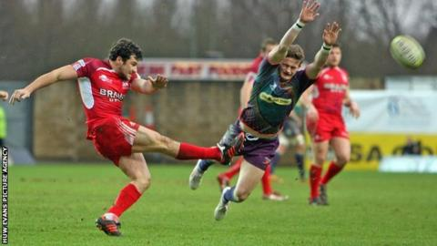 Hallam Amos of Dragons charges down a kick by Ryan Davis of London Welsh