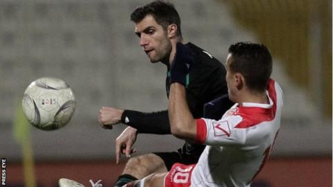 Northern Ireland defender Aaron Hughes competes against Malta's Andrew Cohen