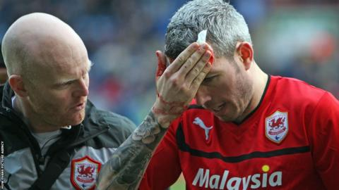 Cardiff City defender Kevin McNaughton leaves the pitch after suffering a cut to the head.
