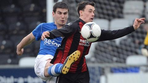 Glenavon defender Mark Haughey challenges Paul Heatley who scored a hat-trick for Crusaders in their 4-1 victory