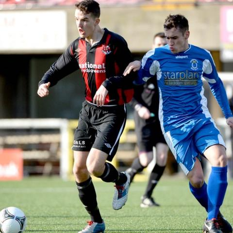 Josh Robinson of Crusaders on the ball against Dungannon Swifts opponent Johnny Topley