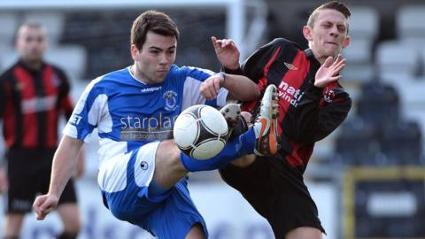Dungannon's Ryan O'Neill and Matthew Snoddy of Crusaders battle for the ball at Seaview