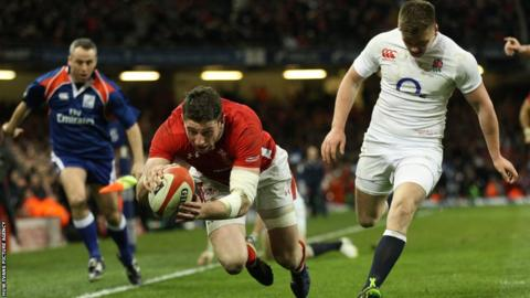 Wing Alex Cuthbert bursts around opposite number Mike Brown to score Wales' first try in their Six Nations title showdown against England at the Millennium Stadium