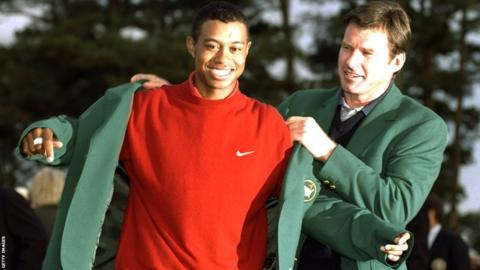 Tiger Woods is presented with his first Green Jacket by Nick Faldo