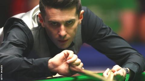 Mark Selby plays a shot with the rest during the Masters in January