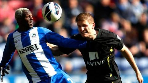 Arouna Kone (left) of Wigan in action with Michael Turner of Norwich
