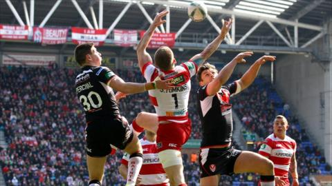Sam Tomkins of Wigan jumps with St Helens' Mark Percival and Jon Wilkin
