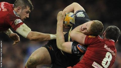 Patrick Leach of Newport Gwent Dragons is tackled by Rob McCusker of Scarlets