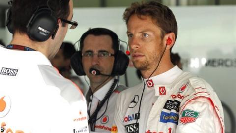 Jenson Button in discussion with his McLaren team