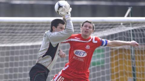 Glens keeper Elliott Morris makes a clean catch despite the close presence of Kevin Braniff