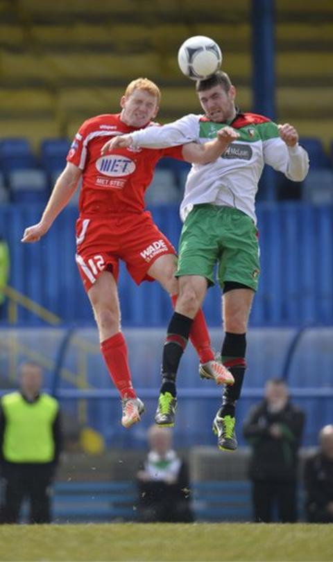 Joesph McNeill loses out in this aerial duel with Glentoran midfielder Mark Clarke