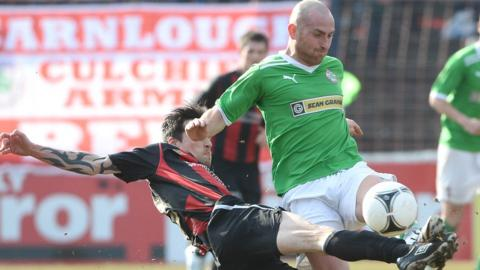 Crusaders midfielder Declan Caddell at full stretch to tackle Cliftonville opponent Barry Johnston at the Oval