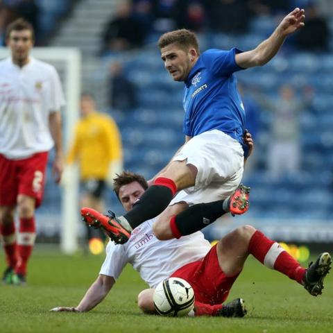 Linfield's Jamie Mulgrew tackles Kyle Hutton of Rangers during the 10 April friendly match at Ibrox Park. The Scottish club staged the match as a thank-you because Linfield had hosted a fund-raising fixture between the sides last year.