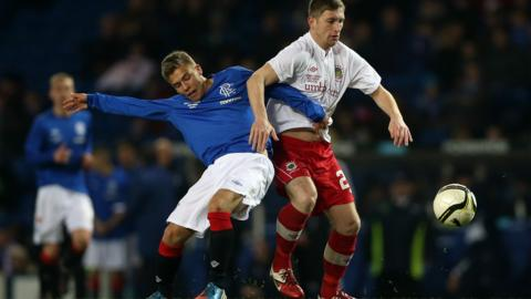 Andrew Murdoch of Rangers challenges Linfield forward Mark McAllister during the friendly in Glasgow