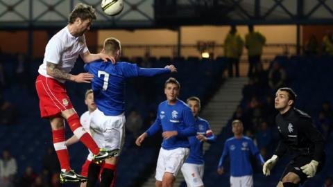 Linfield midfielder Ryan Henderson gets a header in during the friendly fixture against Rangers