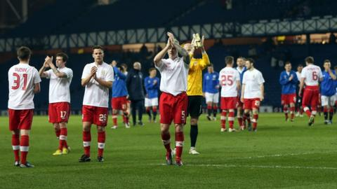 Linfield players acknowledge the support of their travelling fans after the friendly match in Glasgow which hosts Rangers won 2-0