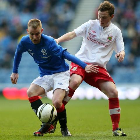 Andrew Mitchell of Rangers competes with Linfield defender Reece Glendinning of Linfield