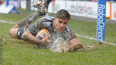 Gavin Evans sends up spray at the Arms Park as he scores a try for the Cardiff Blues.