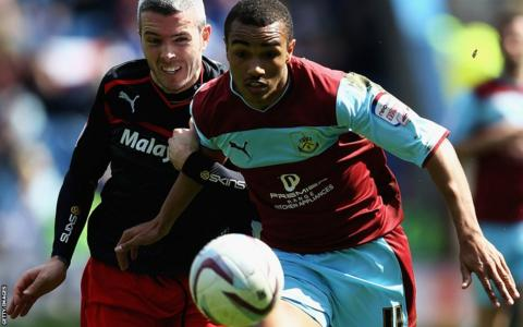 Full-back Kevin McNaughton battles for the ball with Burnley's Junior Stanislas as Premier League bound Cardiff go in search of the Championship title at Turf Moor.