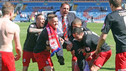 Cardiff City players celebrate winning the Championship title by hoisting manager Malky Mackay on their shoulders.
