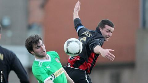 Colin Coates (right) battles with Cliftonville's Jonathan McMurray at Seaview