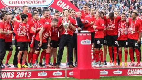 Cardiff City players and staff celebrate after receiving the Championship trophy following the game against Bolton Wanderers.
