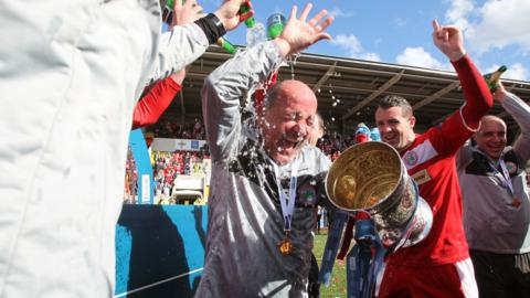 Cliftonville manager Tommy Breslin is covered in champagne on a day of celebration at Solitude