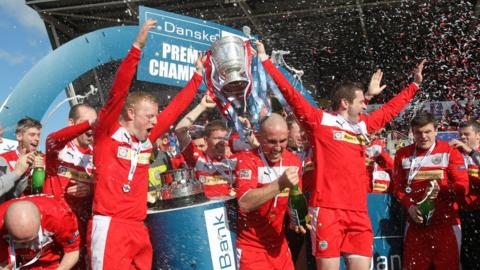George McMullan and Chris Scannell lift the Gibson Cup after Cliftonville's league victory