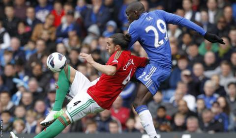 Swansea City defender tangles with Chelsea striker Demba Ba during the Premier League clash at Stamford Bridge.