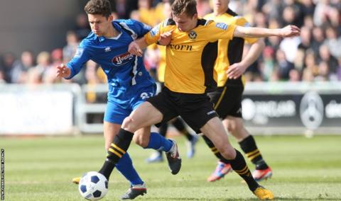 Newport County's Alex Gilbey takes on Grimsby's Andi Thanoj at a packed Rodney Parade